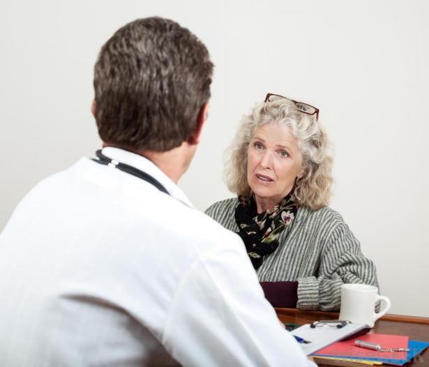 back-of-male-doctor-looking-at-older-female-patient